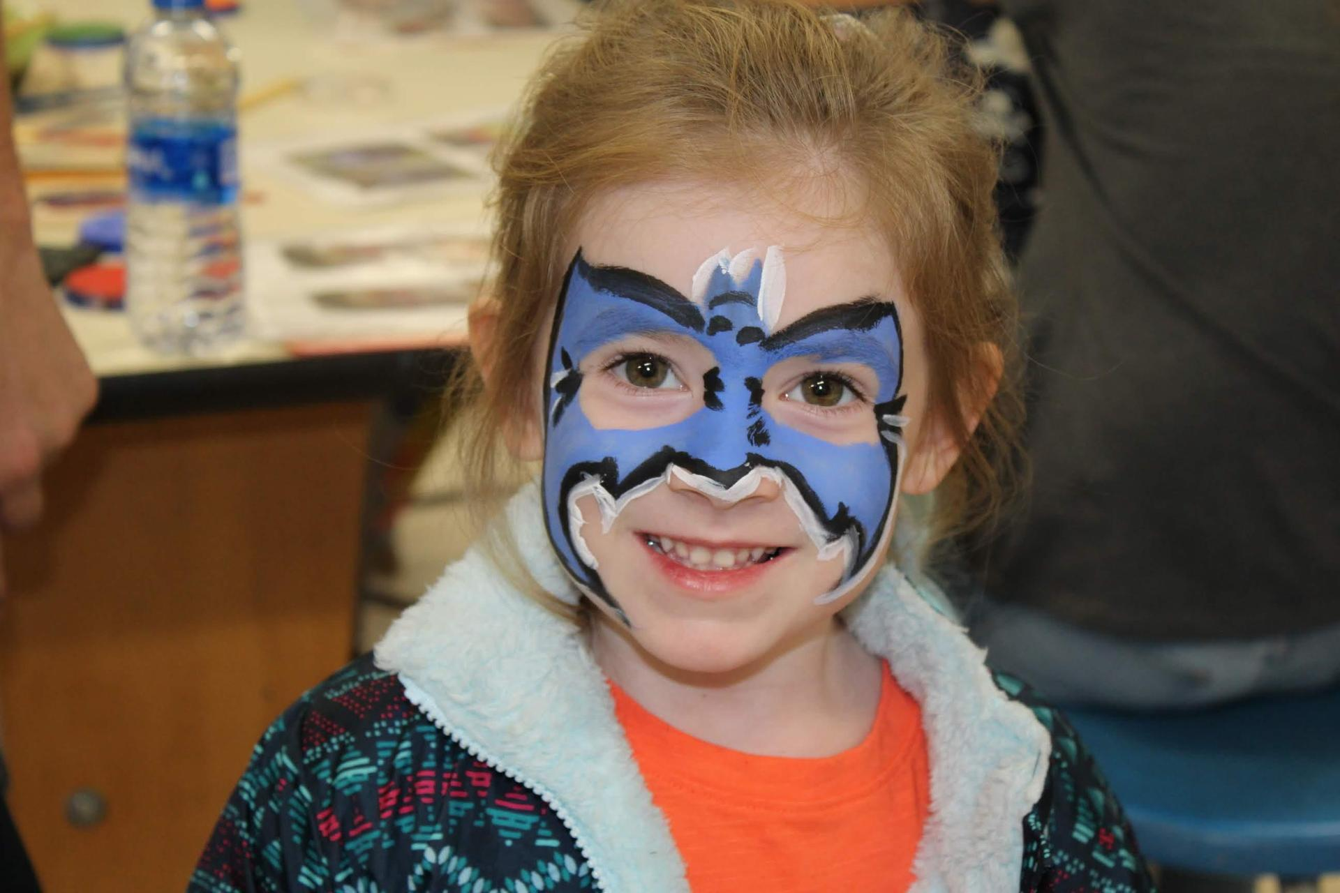Student with flower face paint during fall festival.
