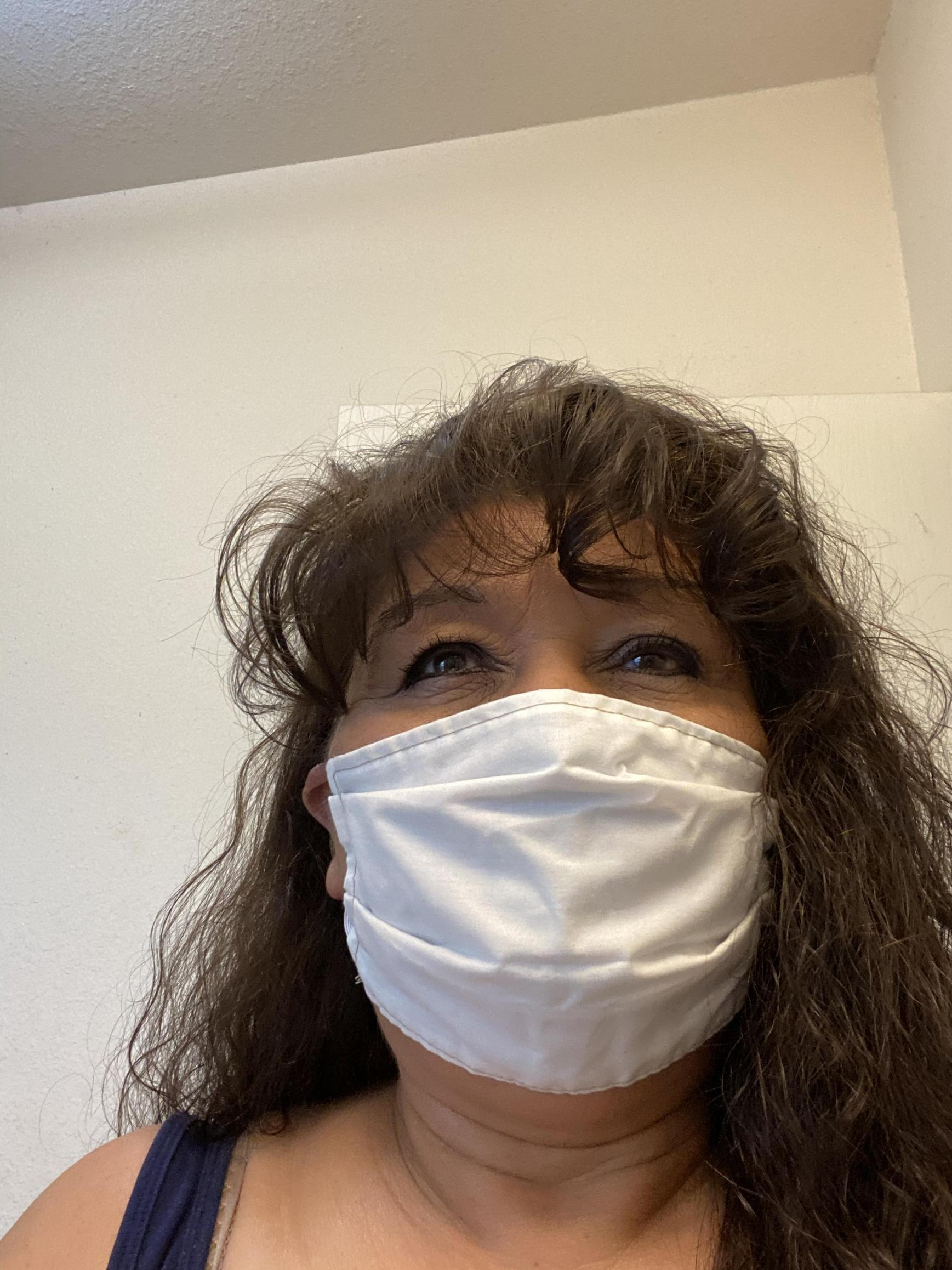 staff member takes selfie wearing mask