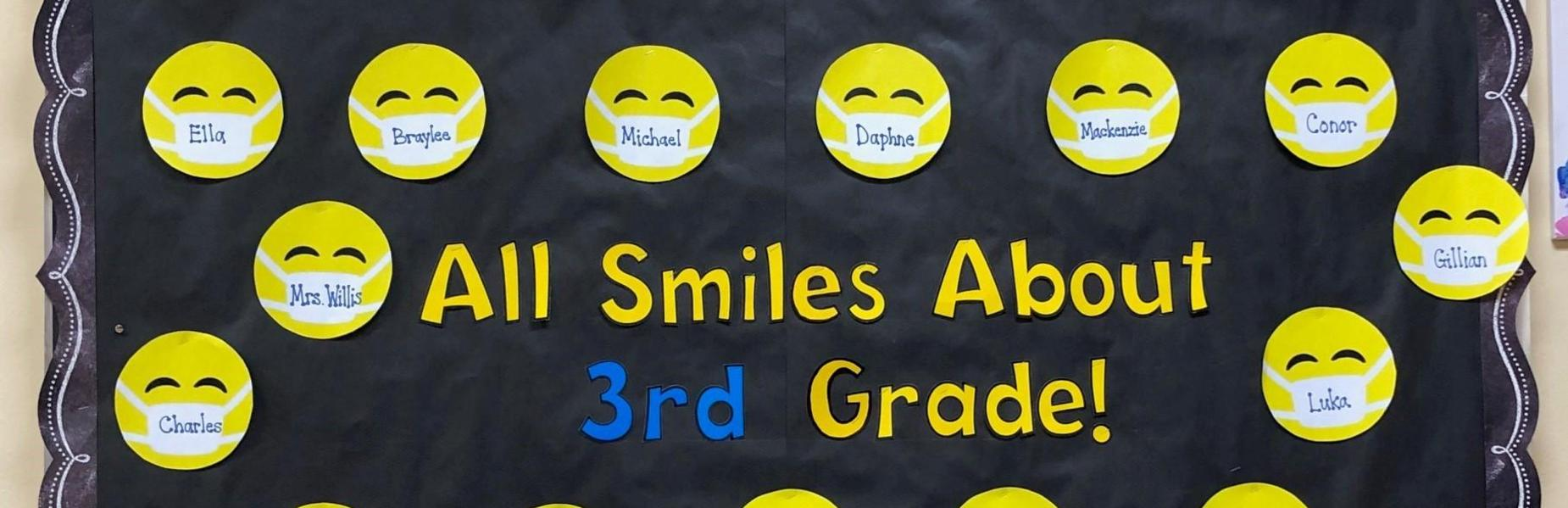 Photo of wilson 3rd grade bulletin with smiling faces wearing masks.