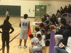 many people sitting on bleachers at a basketball game and players and coaches on the court