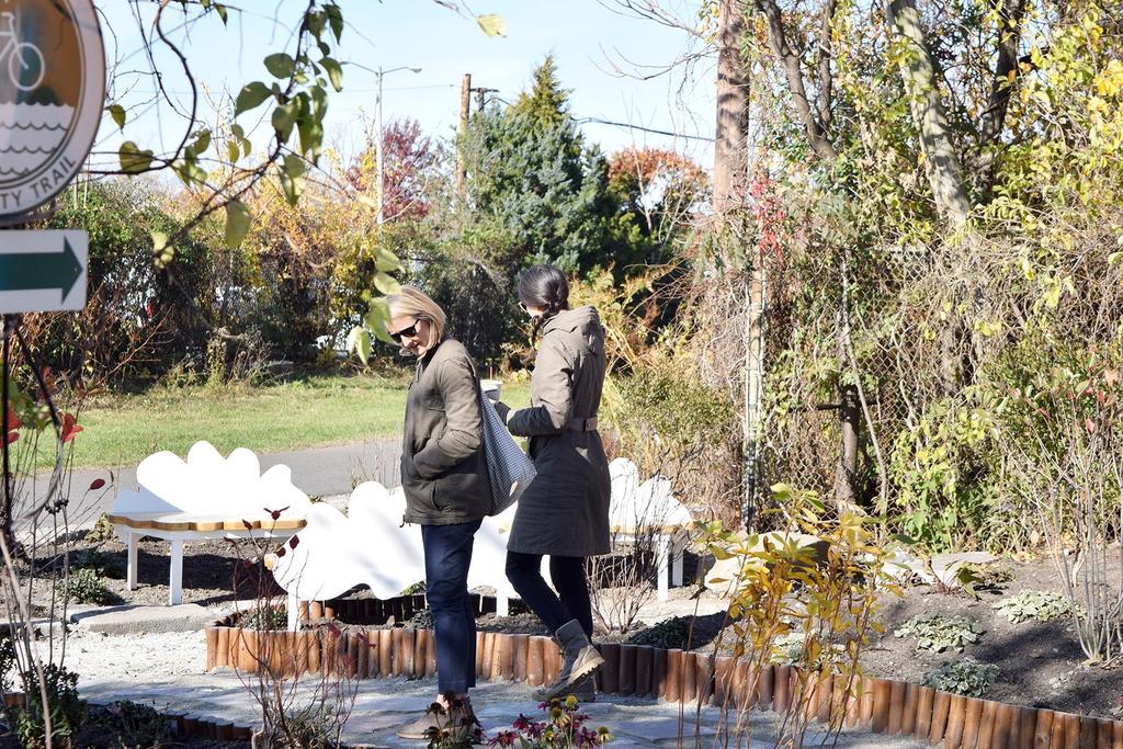 Two women walk on a path that winds through the Jon Norton Rain Garden