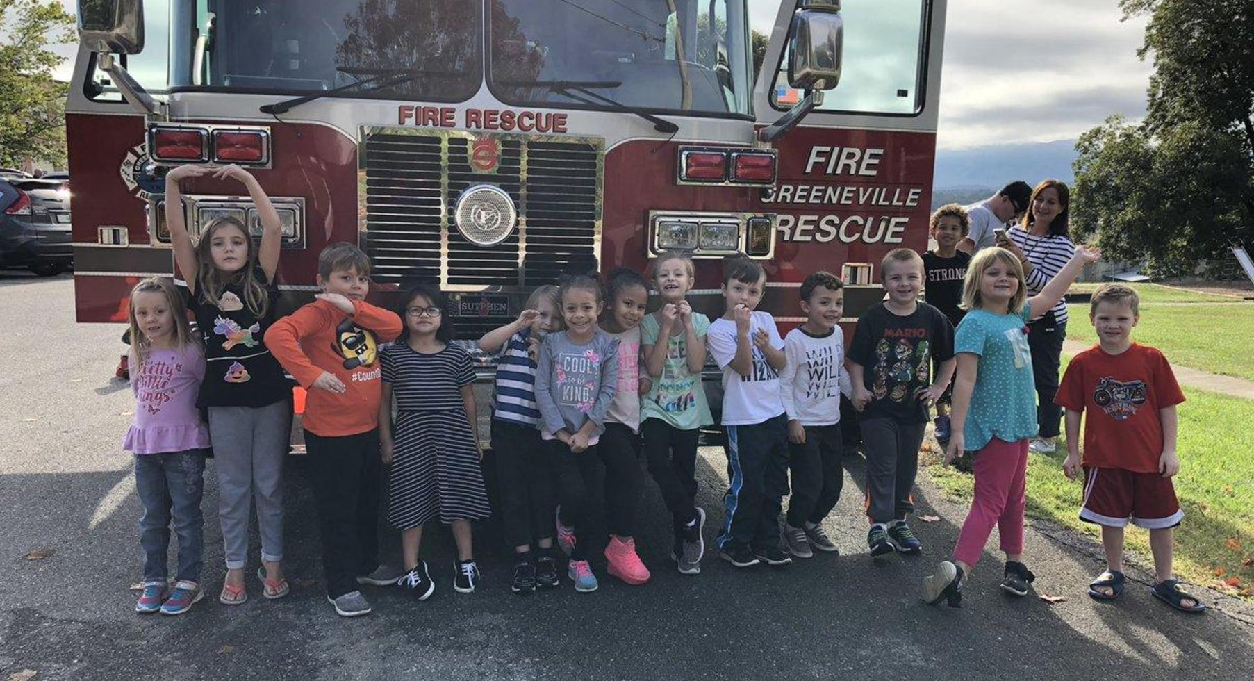 Kindergarten in front of fire truck learning about fire safety.