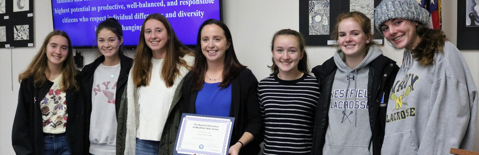 Girls Field Hockey coach Caitlin Cheddar receives recognition at the Dec 4 Board of Education for the program's 400th win.  Coach Cheddar is pictured here with some of her players.