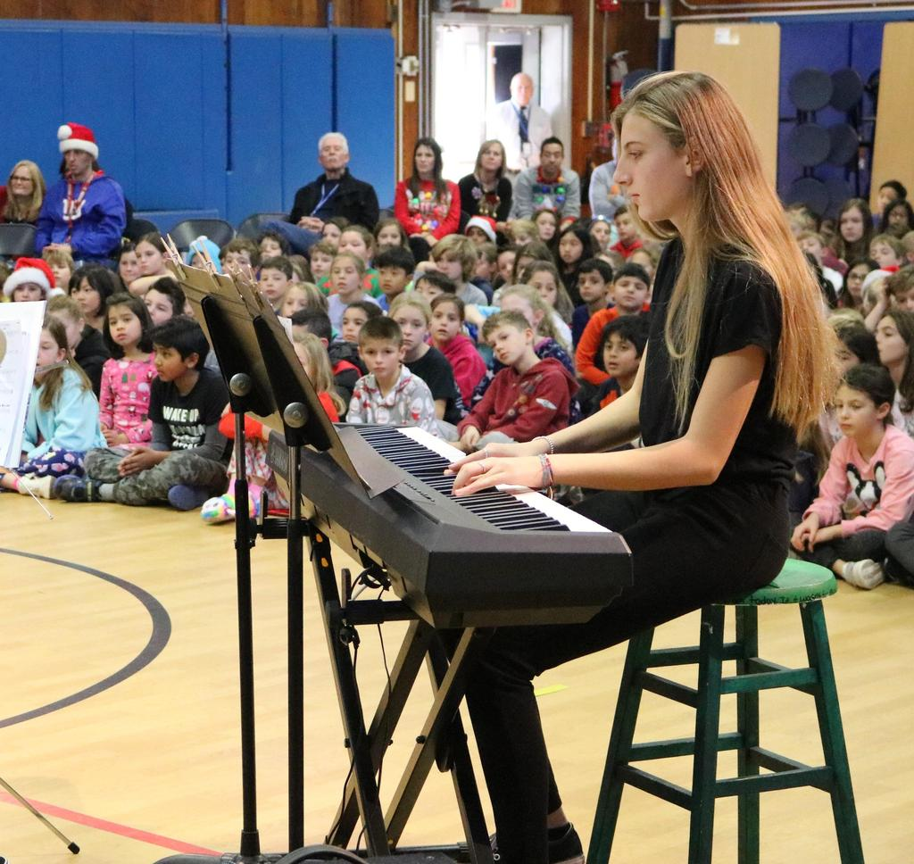 Photo of Roosevelt student pianist in Jazz Band performing for Washington School students.