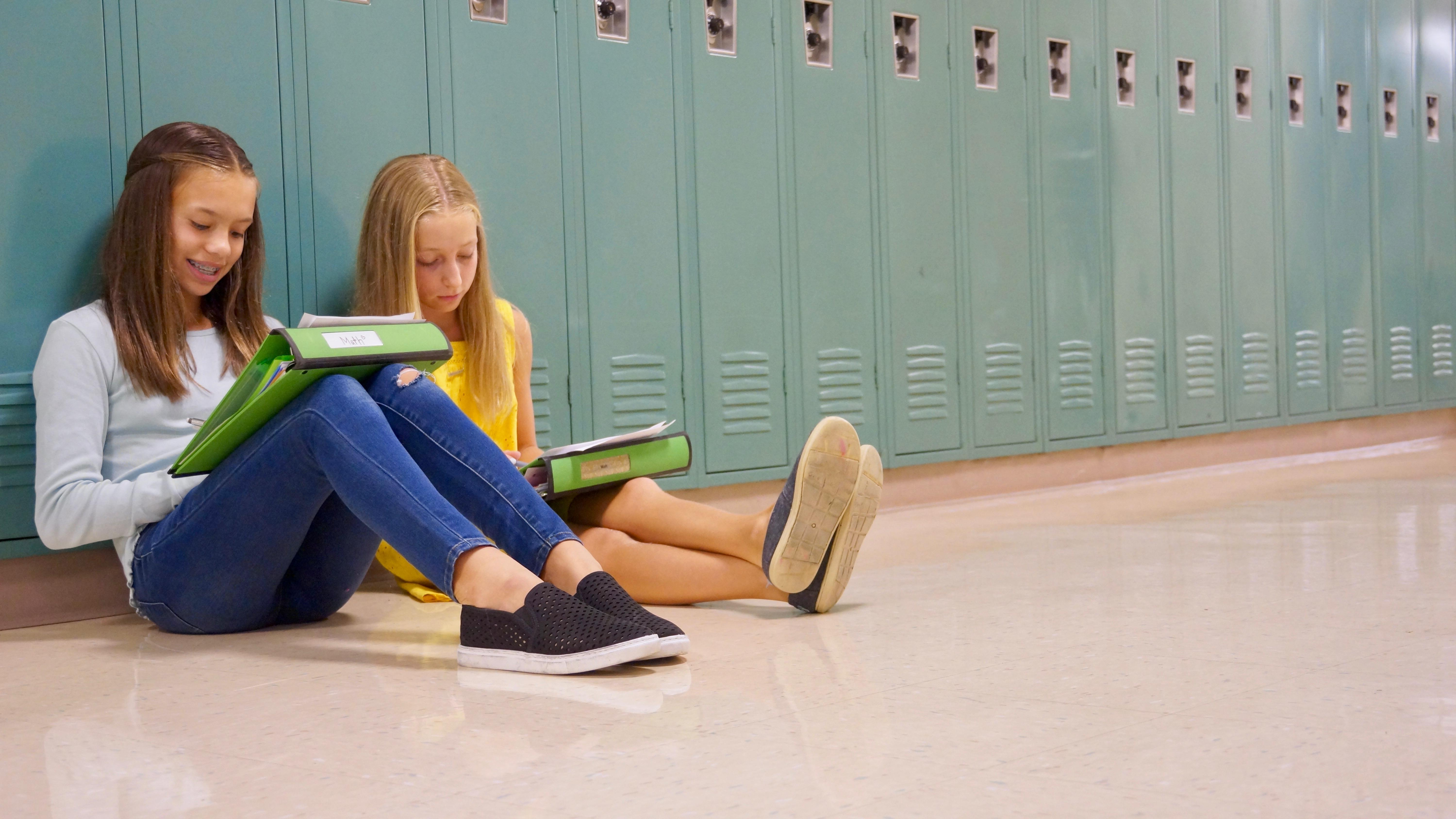 Girls sitting in front of lockers
