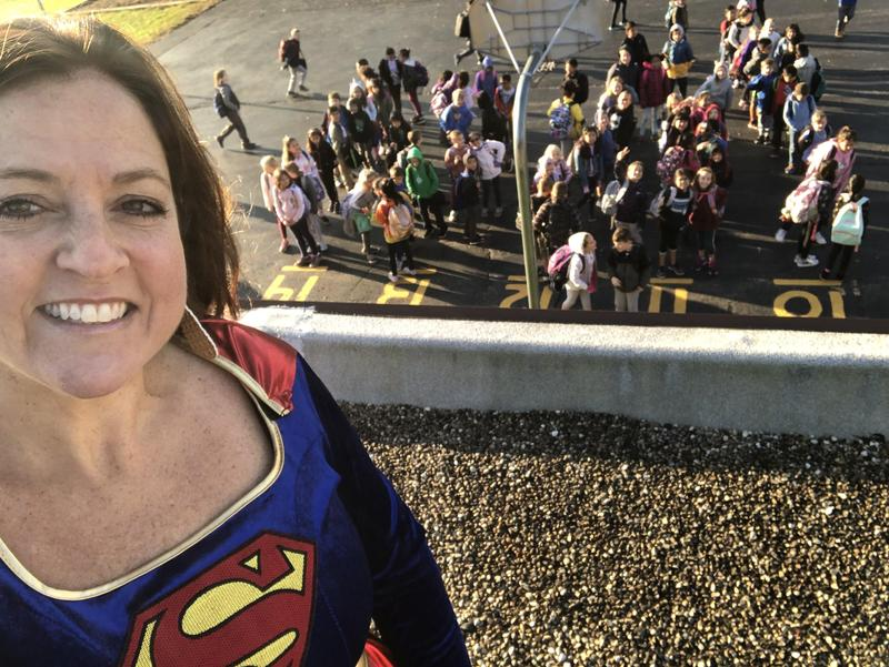 Principal Fergus as Super Girl on top of school with students looking up