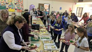 A wide shot of people assembling cookie plates at two tables at WSE.