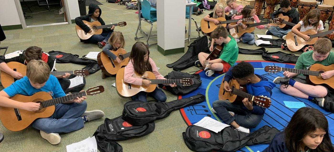 students learning to play guitar