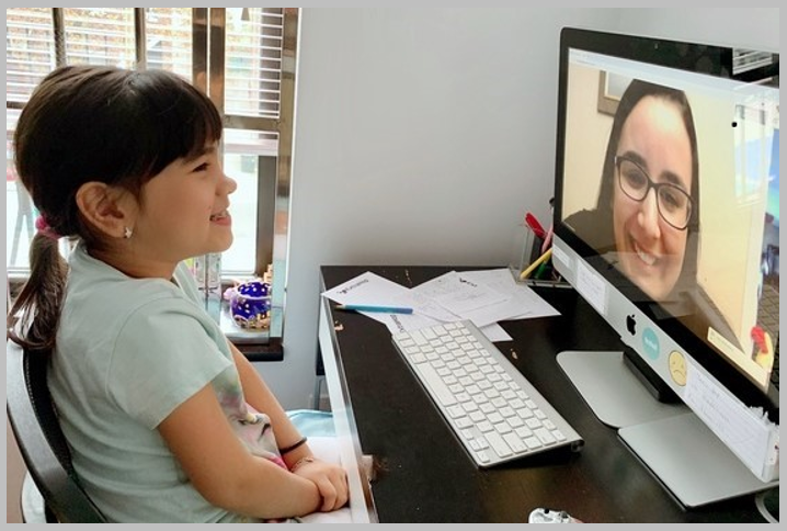 Student sitting in front of home computer, meeting online with her teacher.
