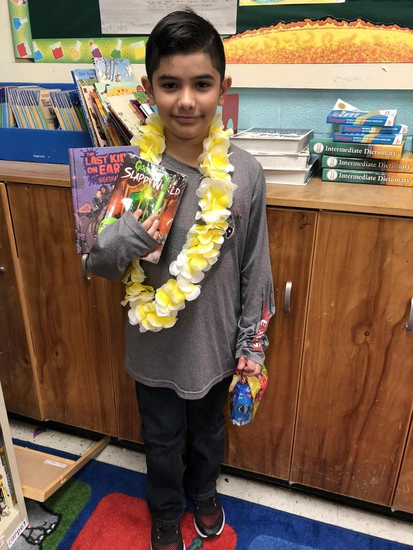 Student holding prizes for becoming a platinum reader.
