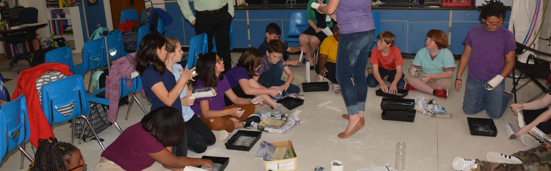 students sitting on floor in classroom doing hands-on activity