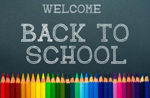 Chalkboard background with Welcome back to school inscribed in chalk and a rainbow of colored pencils across the bottom.