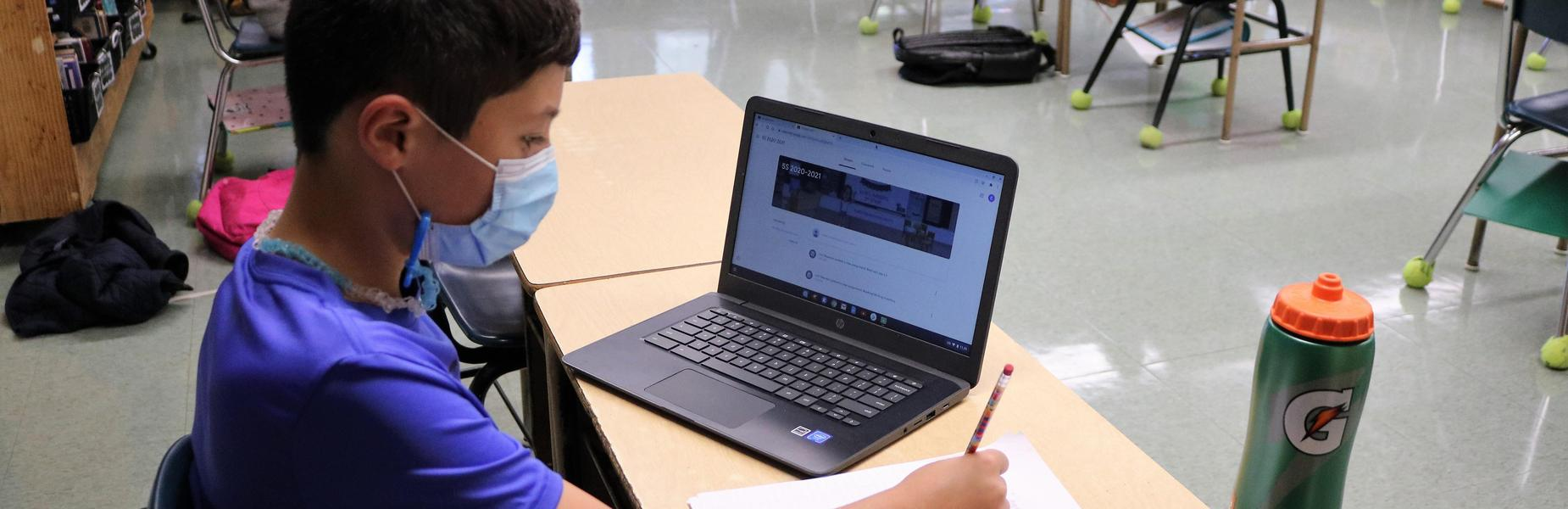 Photo of Tamaques student at desk with laptop and paper and pencil.