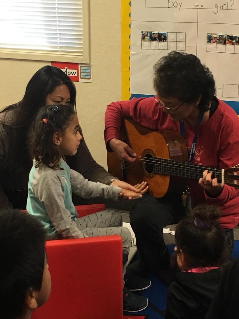 Student playing guitar with Mrs. Arakaki