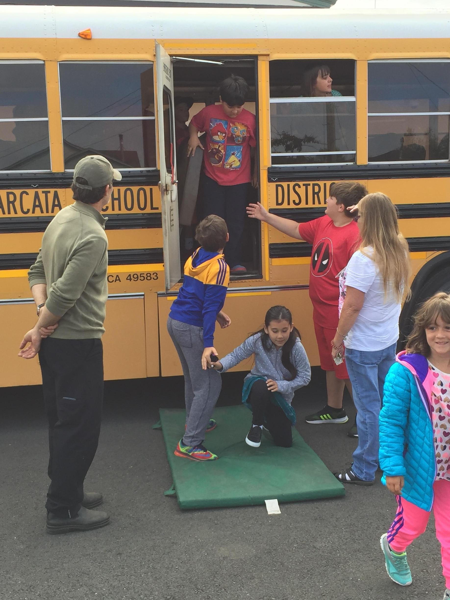 Students participating in bus safety evacuation drill
