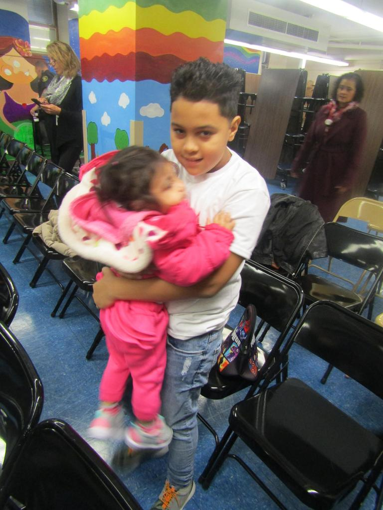 performing 4th grade boy hugging his littler sister