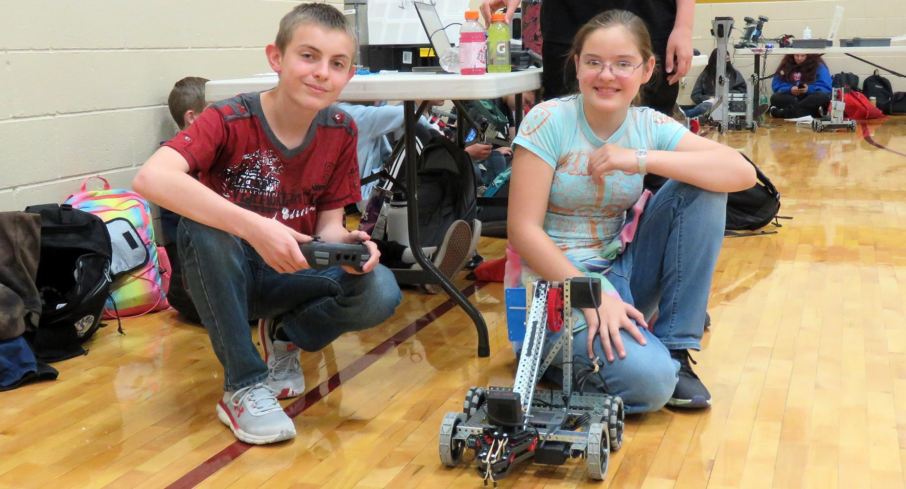 A boy in a red t-shirt and girls in a blue shirt pose with their robot at the East Valley gym.