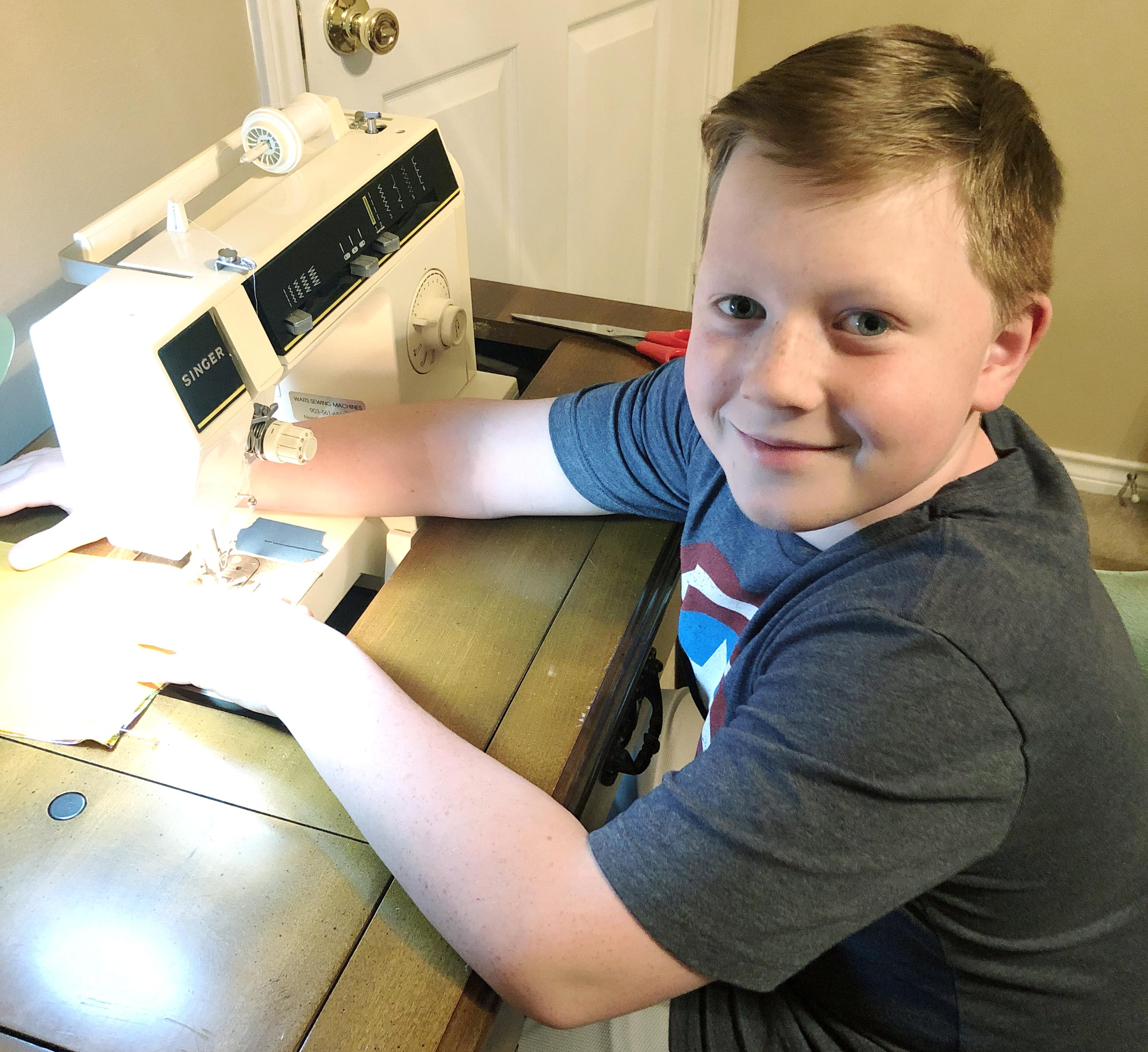 boy sitting at sewing machine