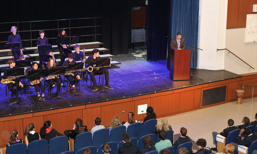 Photo of Roosevelt principal Brian Gechtman introducing Black History Month assembly, with Jazz Band members looking on.