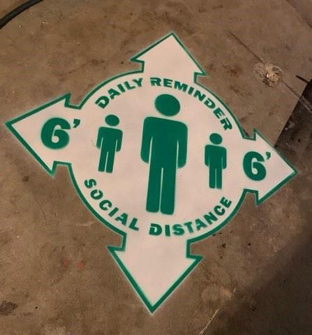 Green and white sticker on cement to remind students of 6 feet social distancing