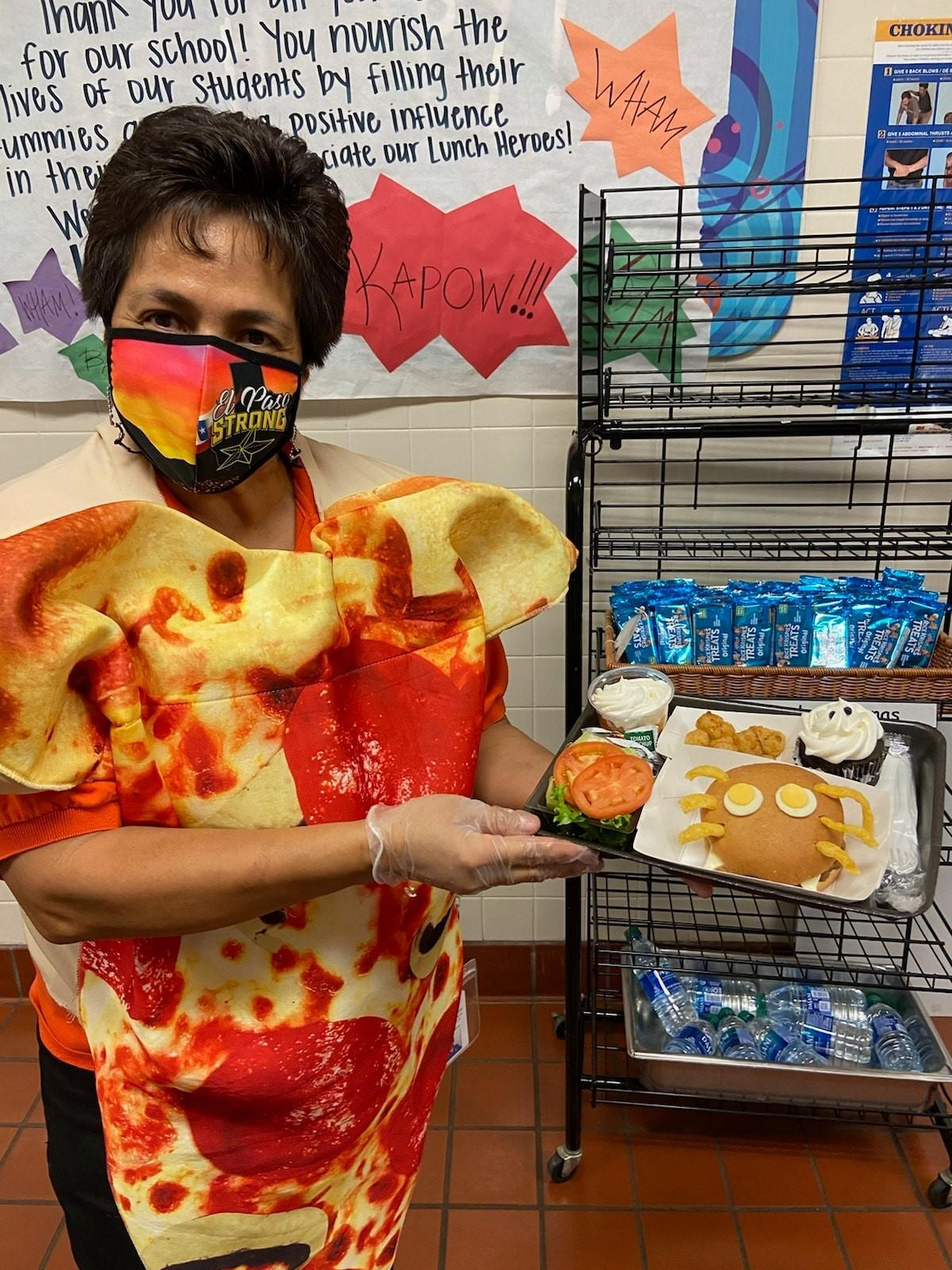 lunch lady dressed as a piece of pizza holding tray of halloween inspired lunch