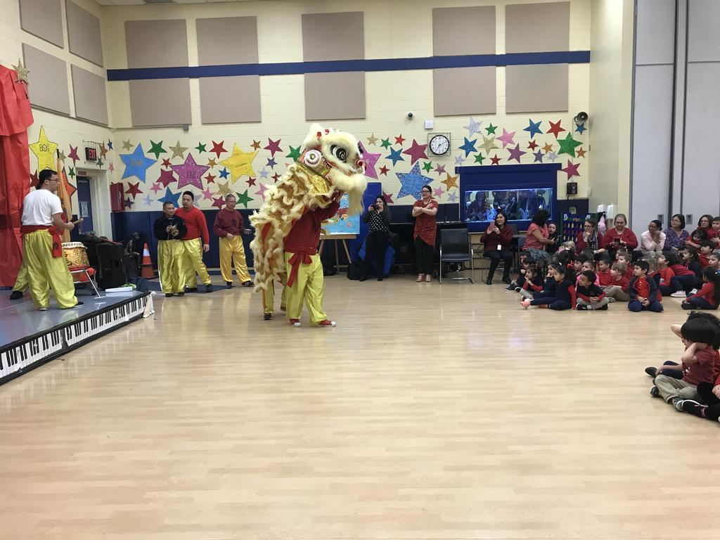 2 men have the dragon costume and are dancing for the students
