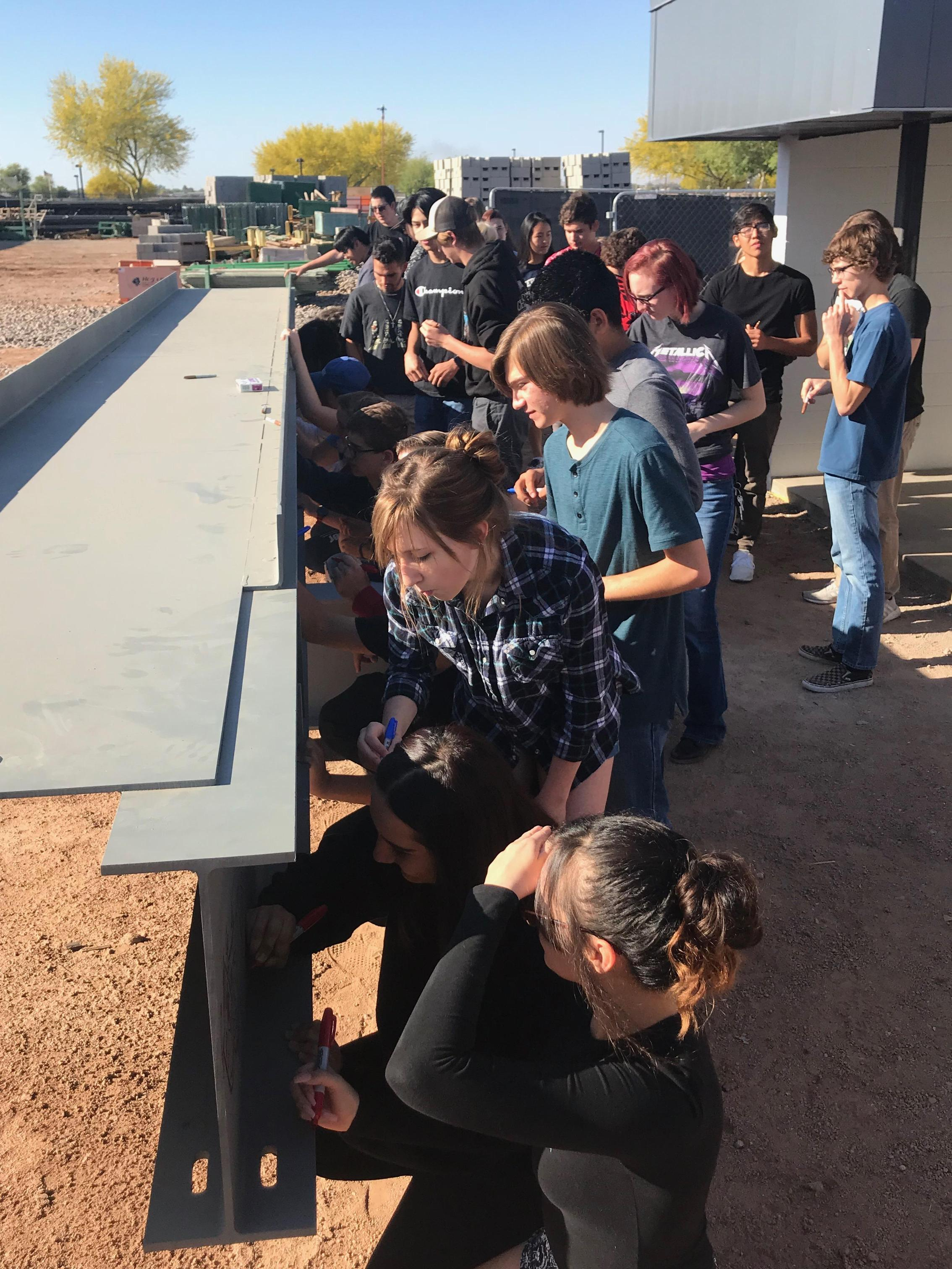 Students signing beam