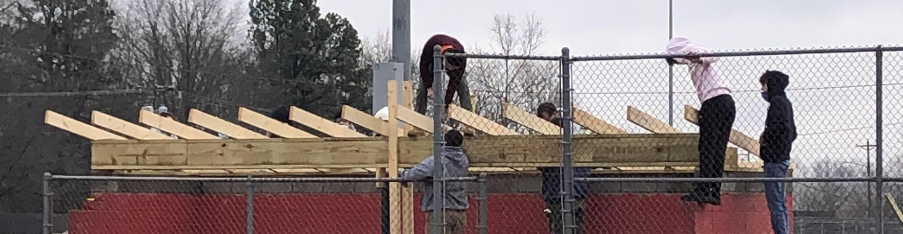 Mr. Hutchins shop class working on putting a new roof on the softball dugouts.