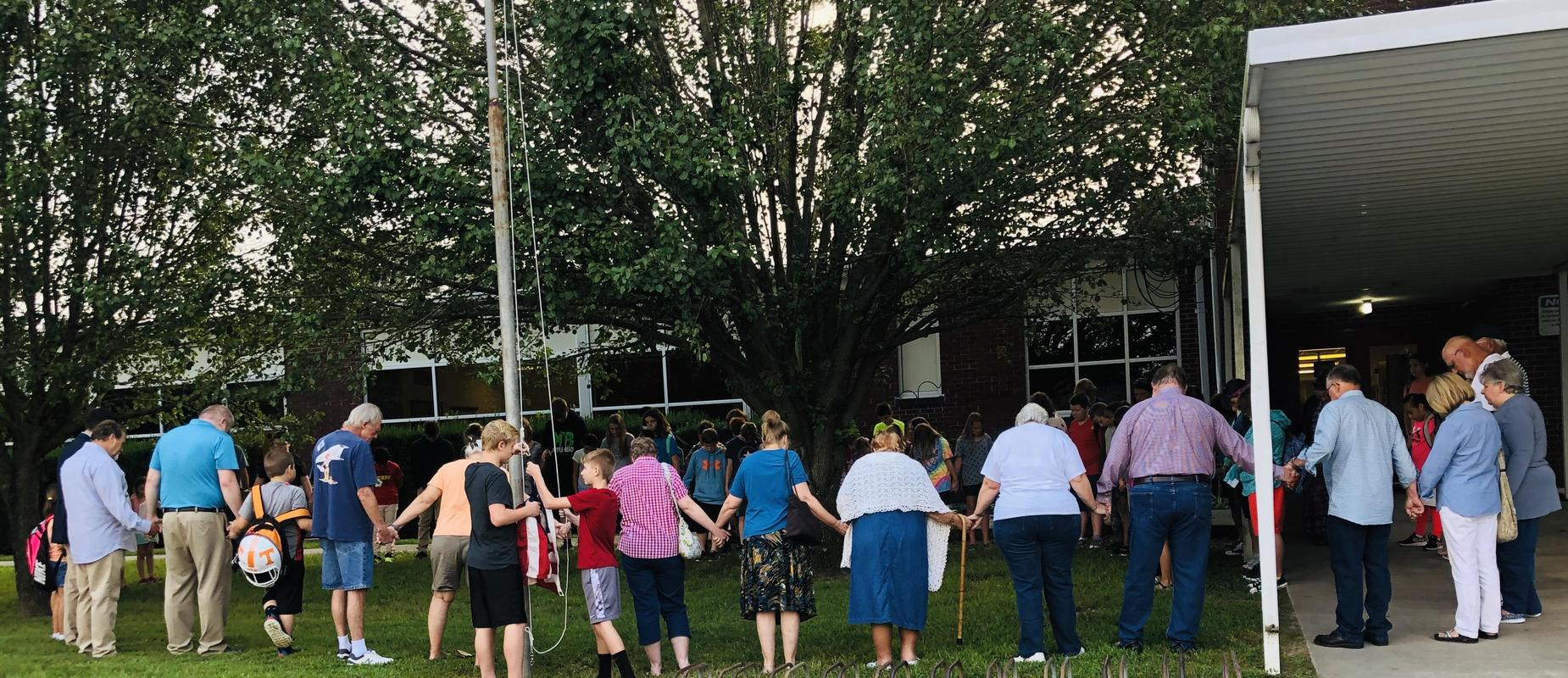 Community Members and some students having prayer around the flag pole