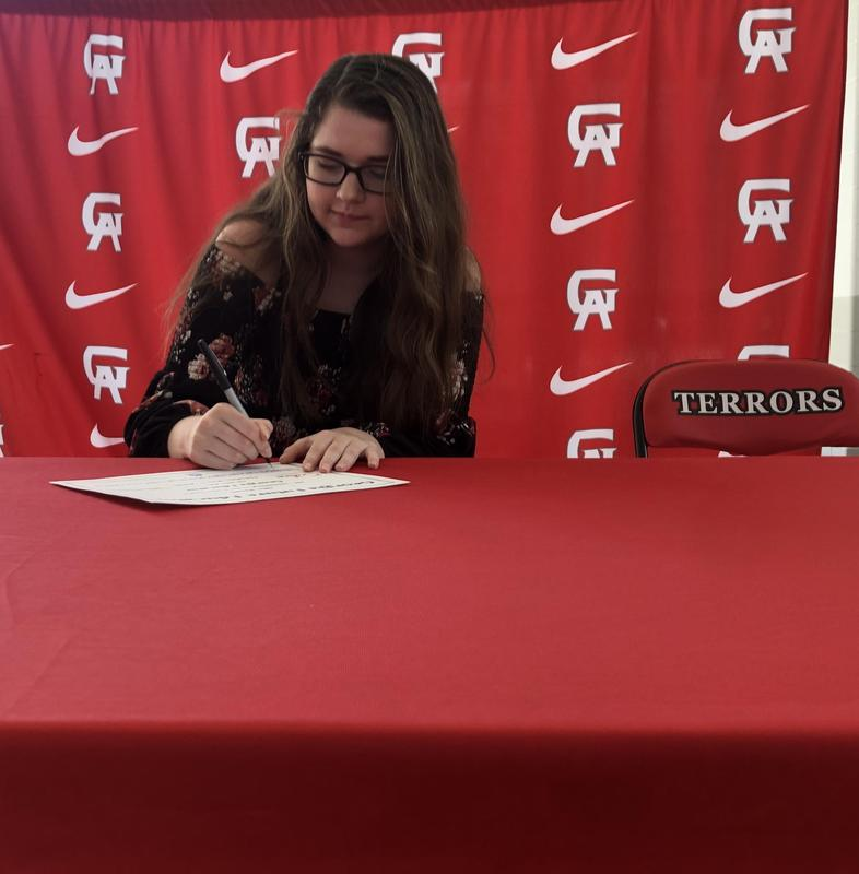 Glynn Academy senior Allie Mason smiles as her mother Sherry Mason takes her picture as she signs a future Georgia educator intent letter Tuesday during a ceremony in the Glynn Academy cafeteria.
