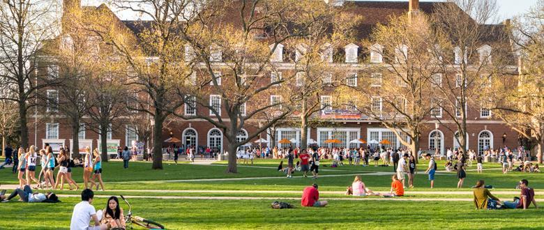 college students sitting outside on grassy field in front of large brick university building