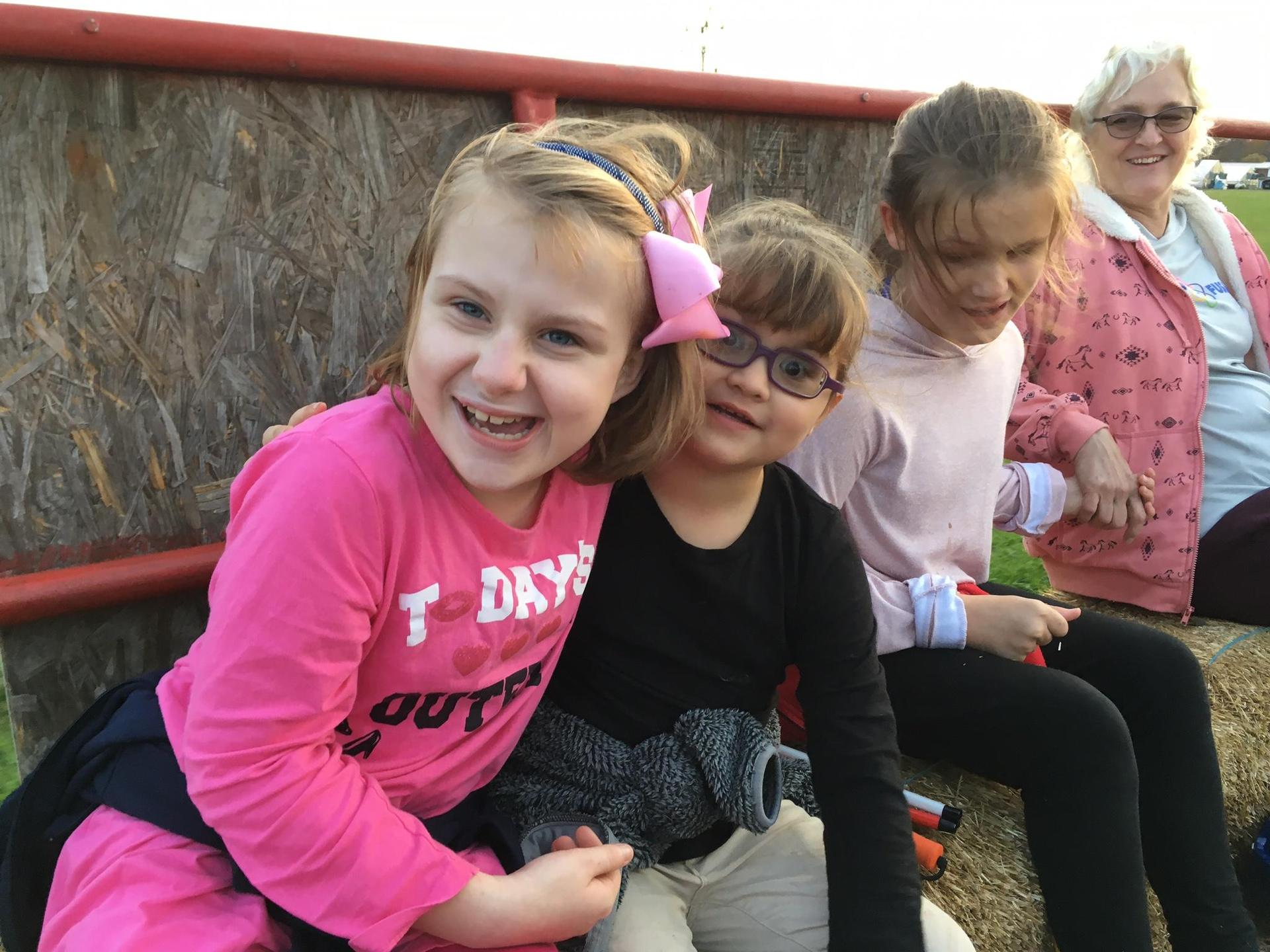 Three female students smile for the camera during the hayride