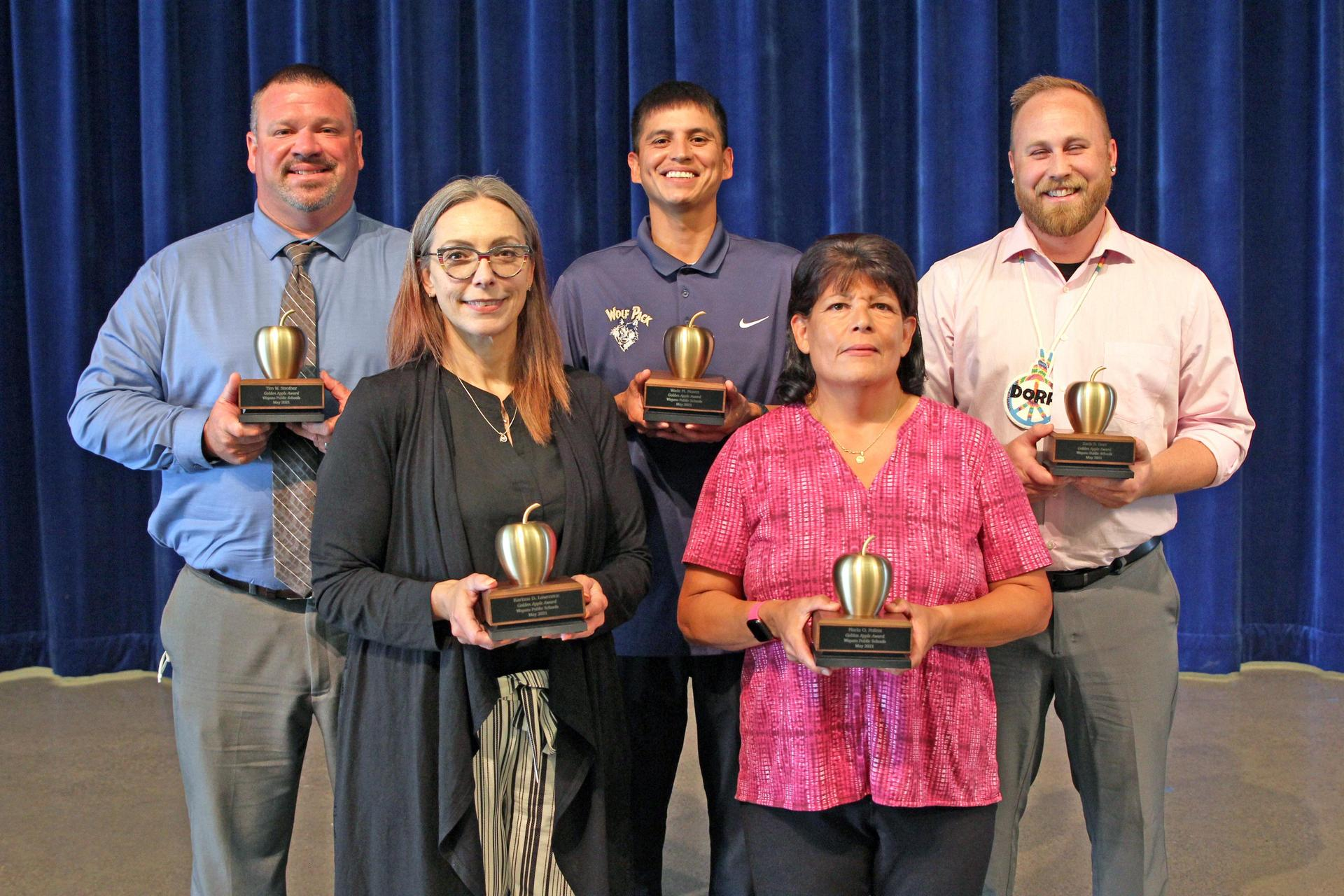 5 staff members holding golden apple awards
