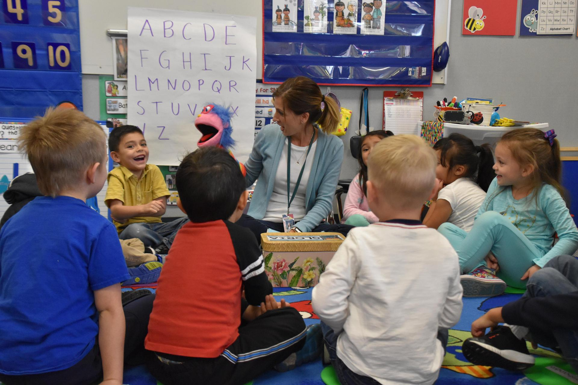 Preschool students learning letter sounds with the class puppet.