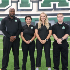 4 adults in matching uniforms on football field