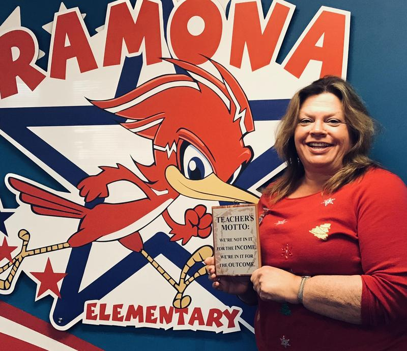 Mrs. Dee Phillips in front of a Ramona sign.