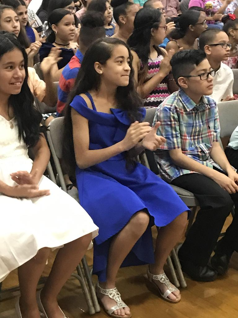 close up of 5th graders in blue dress seated with the other 5th graders