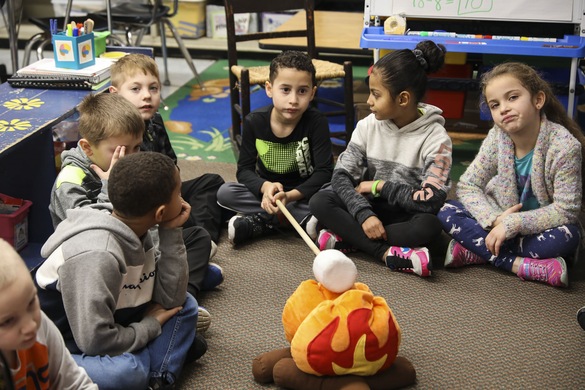 Students meet around the 'campfire' for morning meeting.