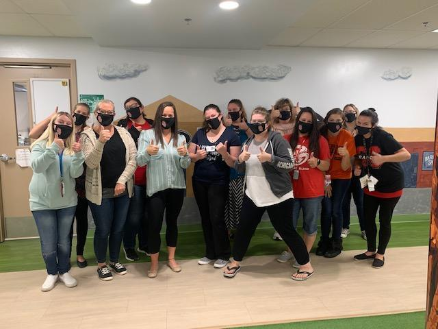 Little Dragons Learning Center staff showing their solidarity toward keeping safe by posing while wearing face masks and giving the 'thumbs up' gesture.