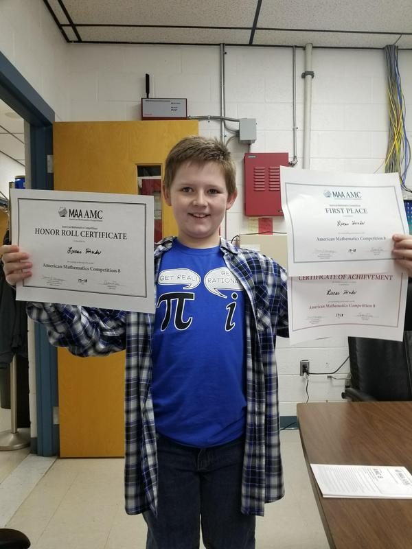 Student Lucas Hinds holding his certificates of achievement