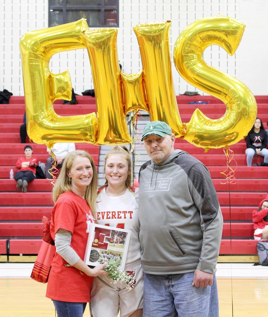 """EHS player and her family, with large """"E-H-S"""" balloons as a backdrop"""