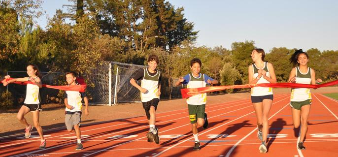 Students Running Through and Breaking Ribbon on Track