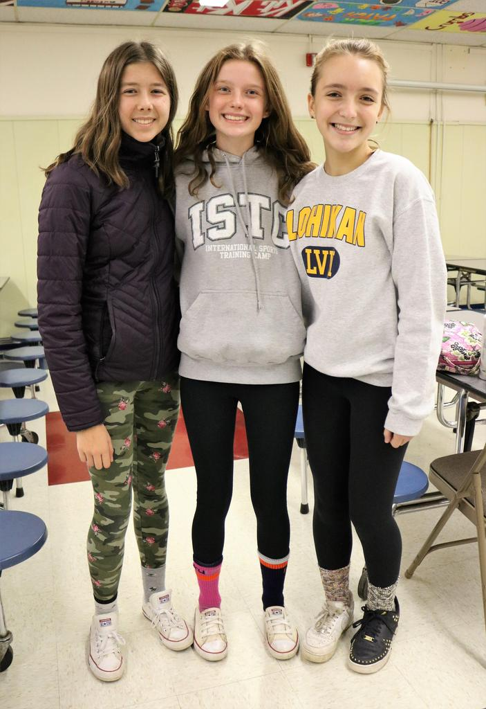 Photo of three Roosevelt students wearing mismatched socks and shoes on Mix It Up Day.