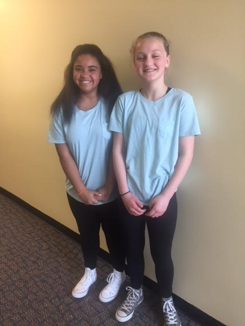 two girls in blue shirts smile for camera