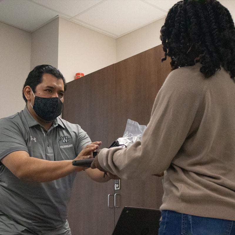 man wearing face mask handing laptop to woman