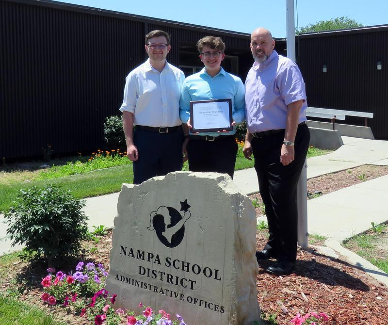 Braeden Watkins poses with Coach Jeffrey Stoppenhagen and Assistant Coach Ben Smoldon in front of the Nampa School District offices.
