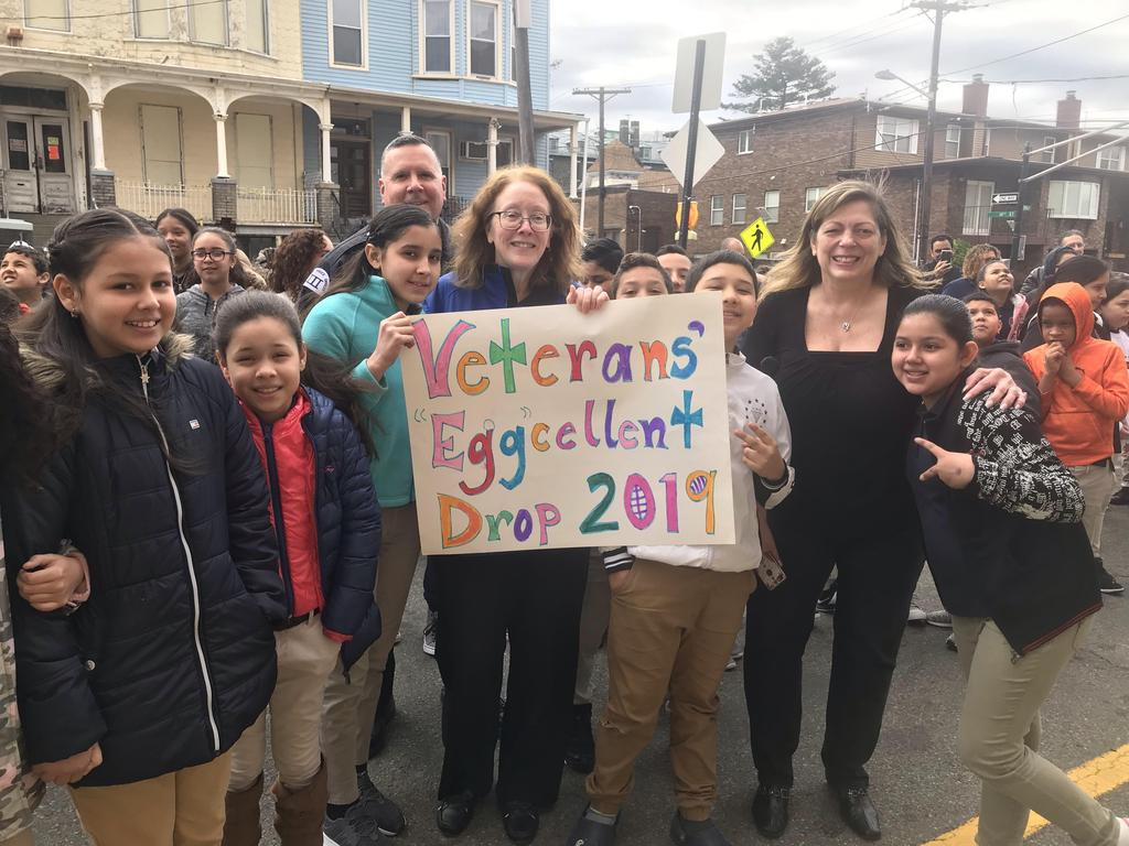 "Principal O'Connell, Mrs. Amar, and the classes around the sign ""Veteran's Egg Drop 2019"""