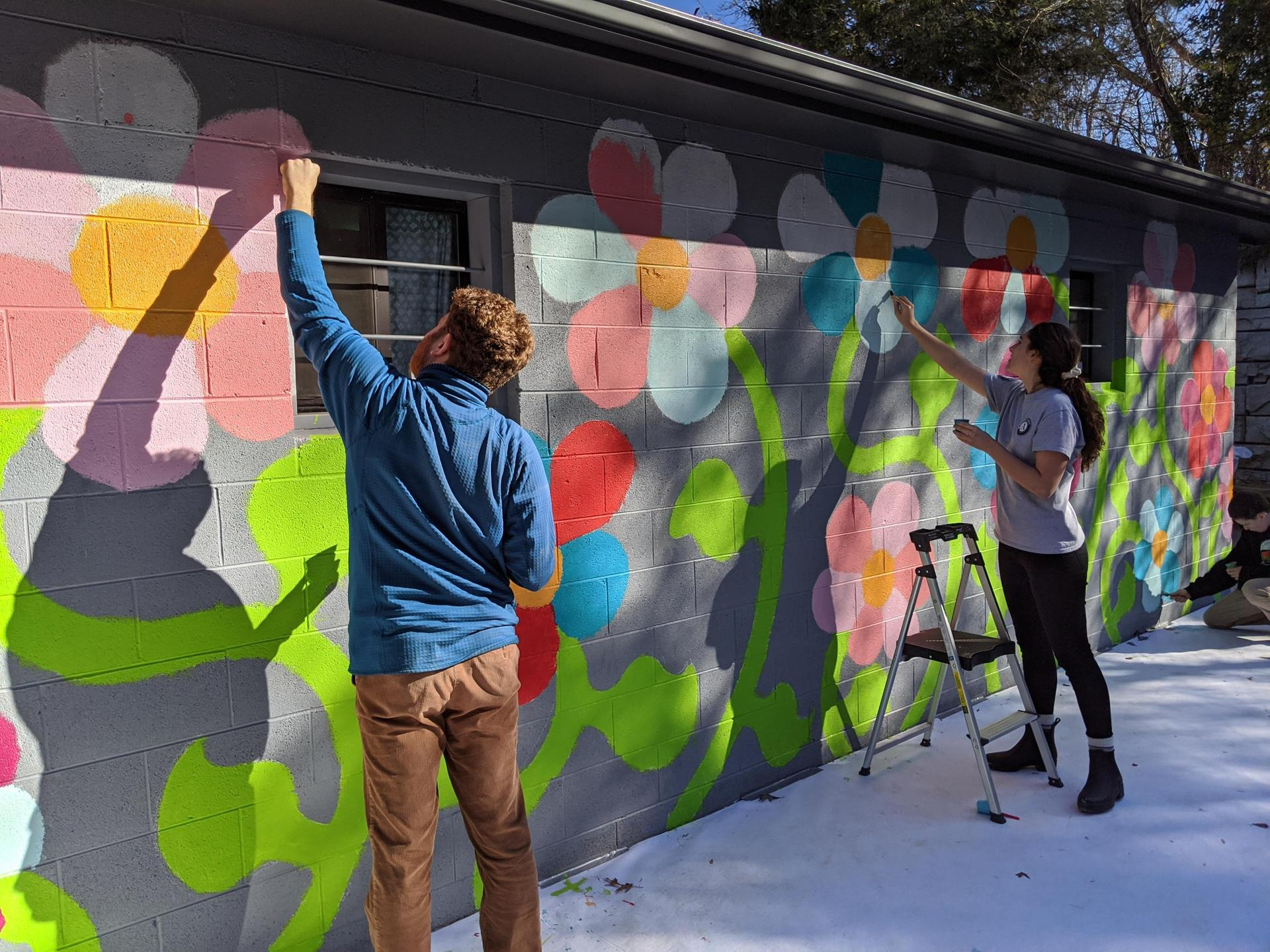 Two ArtSpace members paint a flower mural.