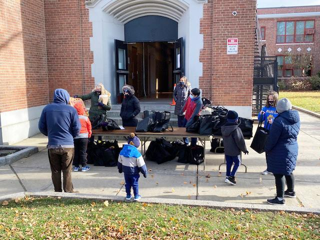 People gather around a table outside the Parlin School