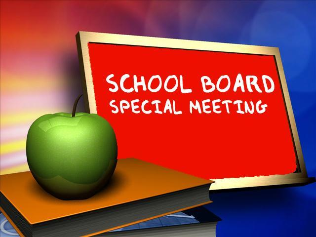 Desk with an apple and chalk board with school board special meeting written